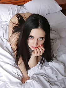 Blue-eyed brunette in white spreading her pussy lips on a white bed